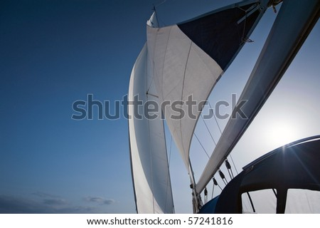 wind in yacht sails with beautiful cloudless sky - stock photo