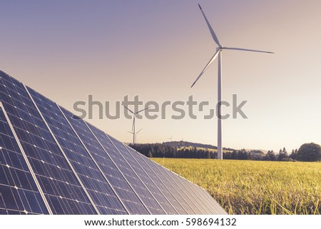 Wind mills and Solar panel at sunset - Ecology and renewable Energy production with sun and wind power