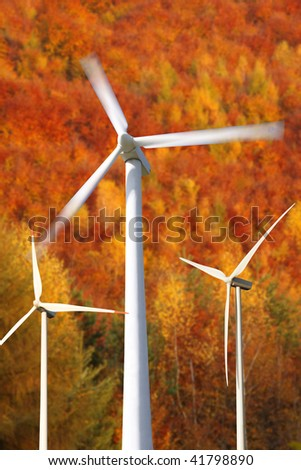 wind mills power generators against autumn forest - stock photo