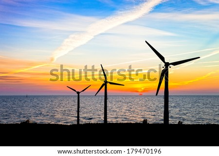 Wind power and colorful sunset over the sea.