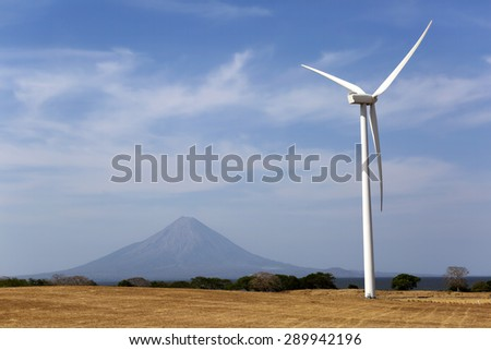wind power generator in Nicaragua with volcano in the background - stock photo