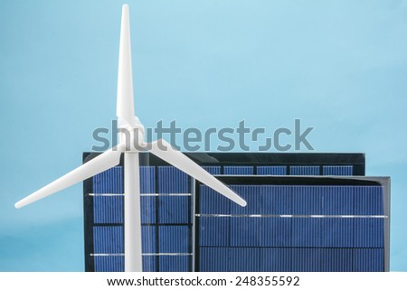 Wind power generator model and solar panel in front of blue background - stock photo
