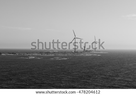 Wind power plants on the island in the sea black and white background