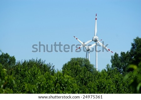 Wind power turbine, forest - blue sky - stock photo