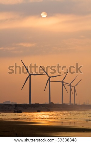 Wind power under sunset near sea shore - stock photo