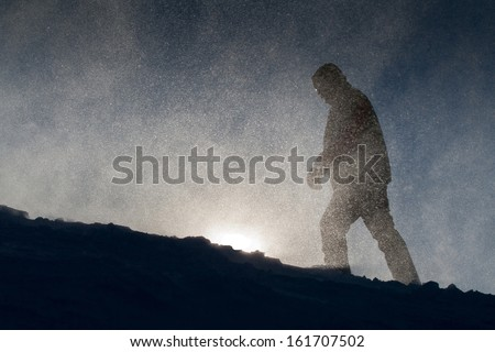 Wind, snow and tourist in the mountains. Yeti silhouette.  - stock photo