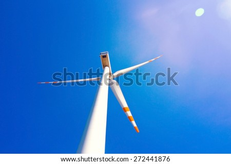 Wind turbine against blue sky. Windmill alternative ecological energy. - stock photo