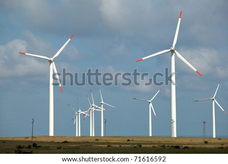 Wind Turbine against blue sky with white clouds produce electricity. - stock photo