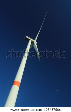 Wind turbine against deep blue sky - vertical orientation - stock photo