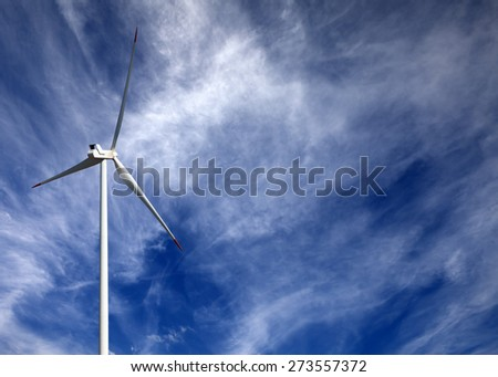 Wind turbine and blue sky with clouds at sun day - stock photo