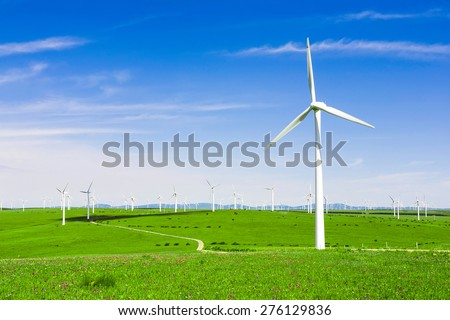 wind turbine and flower meadow under blue sky