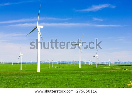 wind turbine and meadow under blue sky - stock photo