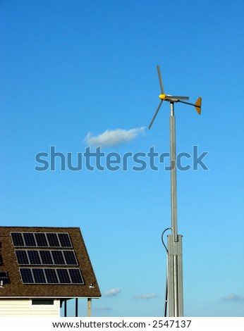 Wind turbine and solar panels on a roof as sustainable renewable energy sources