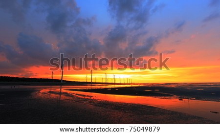 Wind turbine array silhouette at seashore wetland under sunset - stock photo