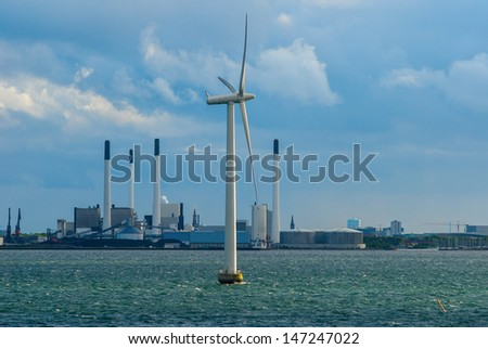 Wind turbine at sea with factory in the background. - stock photo