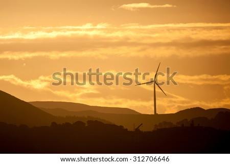 Wind turbine at sunset - stock photo