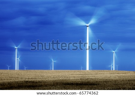 Wind turbine blade spinning like electric pinwheels in the middle of a wide open field. - stock photo