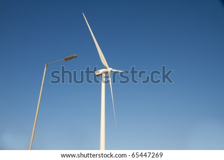 Wind turbine blades alongside electric street light against blue sky