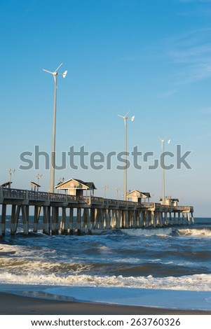 Wind turbine by the ocean for sustainable and renewable electricity - stock photo