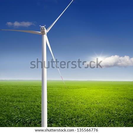 Wind turbine. Electric field on the grass. - stock photo