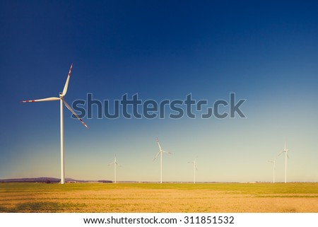 Wind turbine farm, alternative energy, electricity power generators on green field. Clean energy on vintage inspirational summer landscape - stock photo