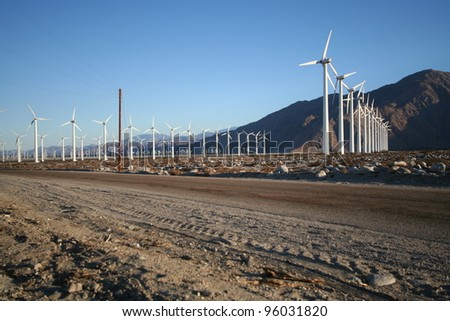 Wind Turbine farm located on California desert surrounded by mountains