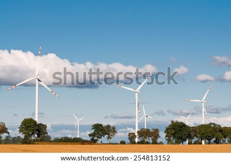 Wind turbine farm on rural terrain - stock photo
