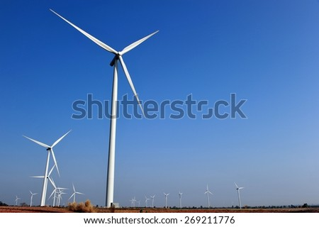 Wind turbine farm with deep gradient blue sky over the tapioca field in Thailand.