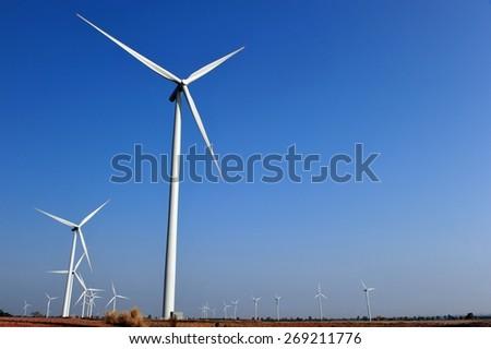 Wind turbine farm with deep gradient blue sky over the tapioca field in Thailand. - stock photo