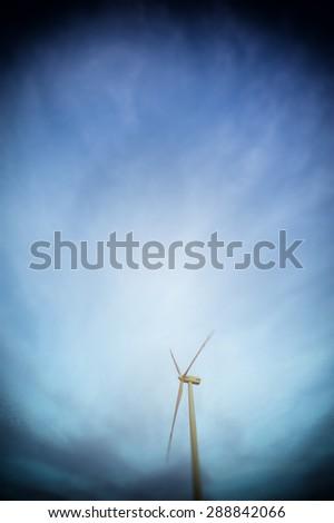 Wind turbine farm with rays of light at sunset - stock photo