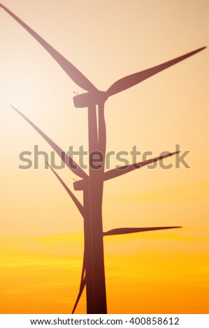 Wind turbine farm with rays of light at sunset - stock photo