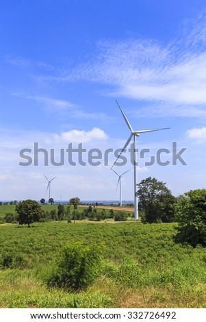 Wind Turbine for alternative energy on background blue sky  - stock photo