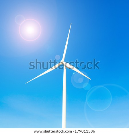 wind turbine generator on blue sky wilt lens flare