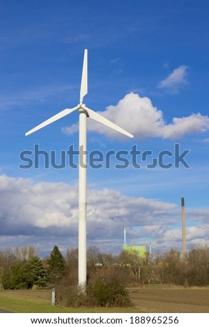 Wind turbine in a field with a factory in the background - stock photo