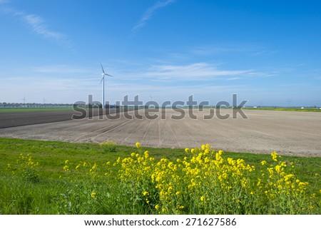 Wind turbine in a plowed field in spring - stock photo