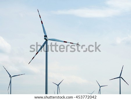 Wind turbine in field. Group of wind turbine. A windfarm or wind park is a group of wind turbines in the same location used to produce electricity. - stock photo