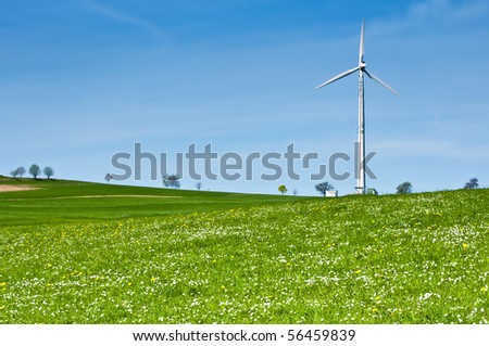 Wind Turbine in Spring Meadow full with Daisies - stock photo
