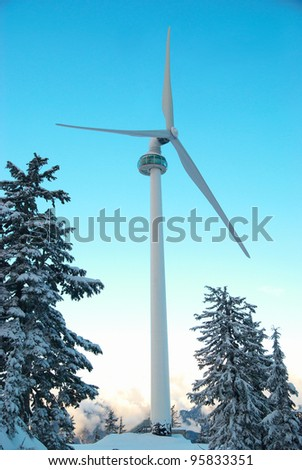Wind turbine in the mountain covered with winter forest - stock photo