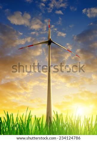 Wind turbine in the sunset - stock photo