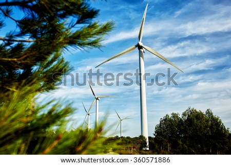 Wind turbine located in a field, windmill standing outside the city, electric generator against cloudy sky at day, renewable and alternative energy sources - stock photo