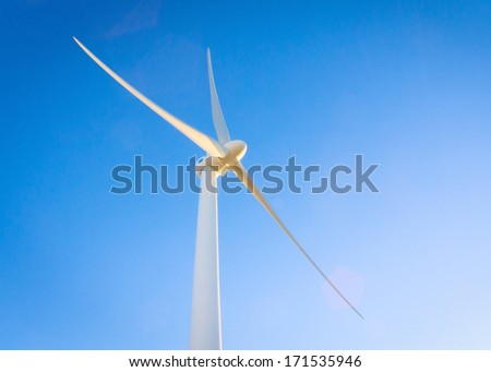 Wind turbine on blue sky with copy space - stock photo