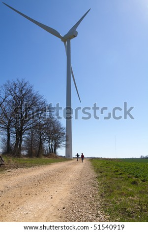 Wind turbine on clear blue sky with running children on a road - stock photo