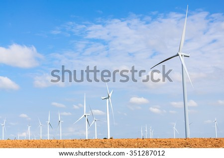 Wind turbine on the green meadow over the blue clouded sky - stock photo