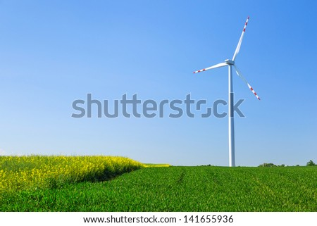 Wind turbine over blue sky on the summer field - stock photo