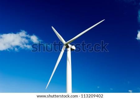 Wind turbine over the deep blue sky - stock photo