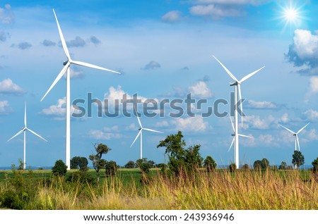 Wind turbine power generator on blue sky - stock photo
