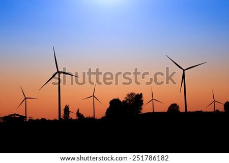 Wind turbine power generator silhouette at sunset - stock photo