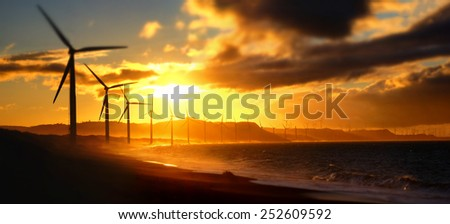 Wind turbine power generators silhouettes at ocean coastline at sunset. Alternative renewable energy production in Philippines. Two images panorama, tilt shift effect - stock photo