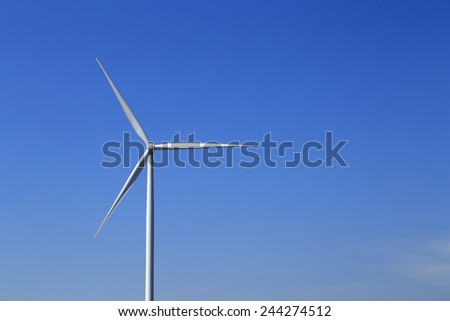 Wind turbine producing alternative energy with blue sky