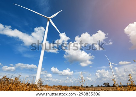Wind turbine with blue sky, summer field, renewable energy  - stock photo